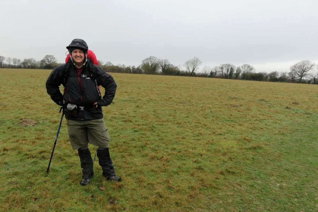 person in field in gaiters and raincoat
