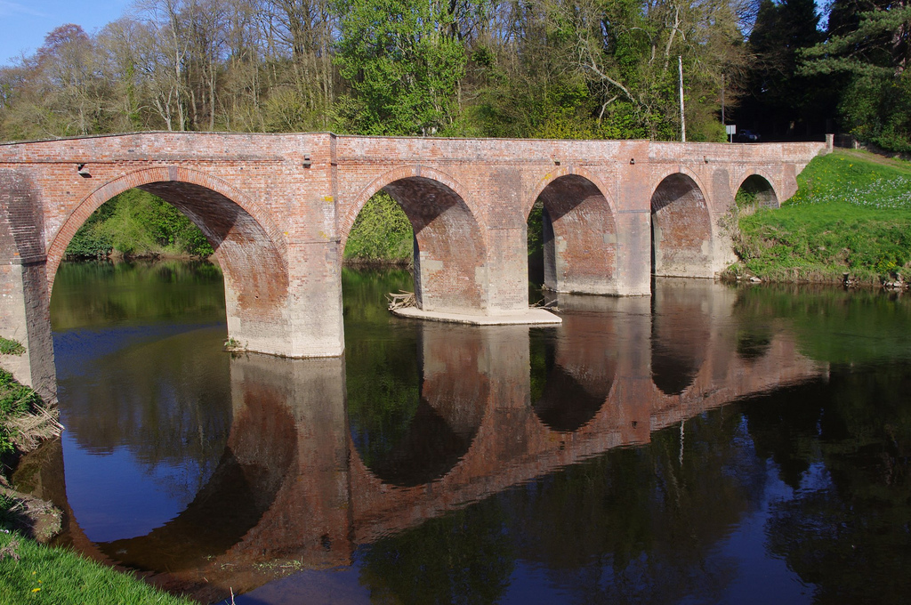 Red brick bridge with arches over river