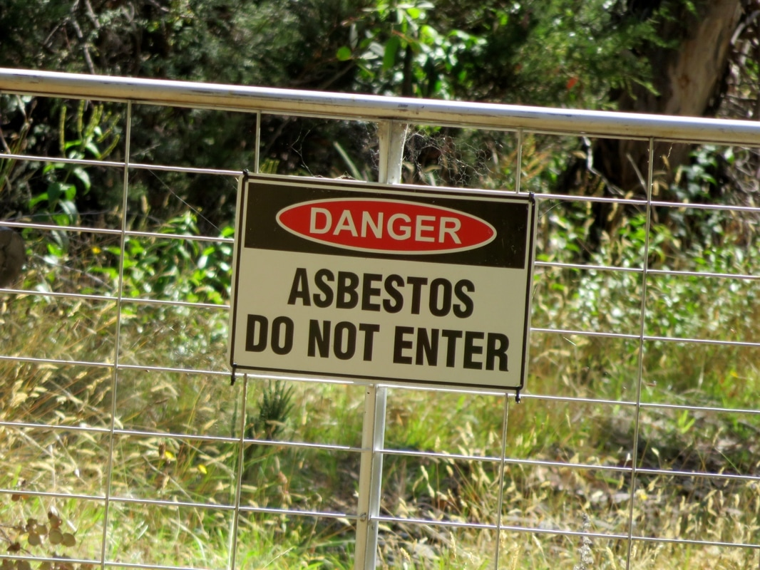Gate with asbestos warning sign