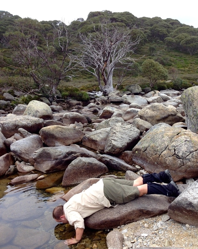 Person lying on rock to drink from stream