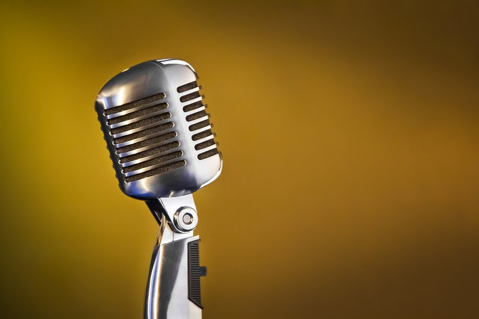 Retro chrome vocal mic on mustard background