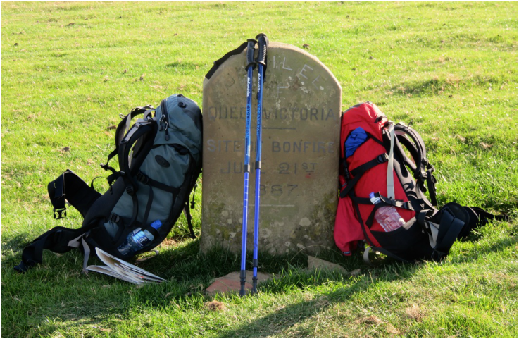 Backpacks leaning on a stone marker