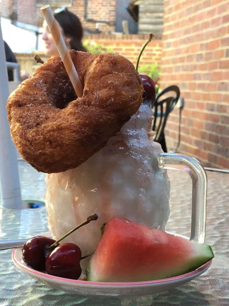 Milkshake topped with doughnut and cherry