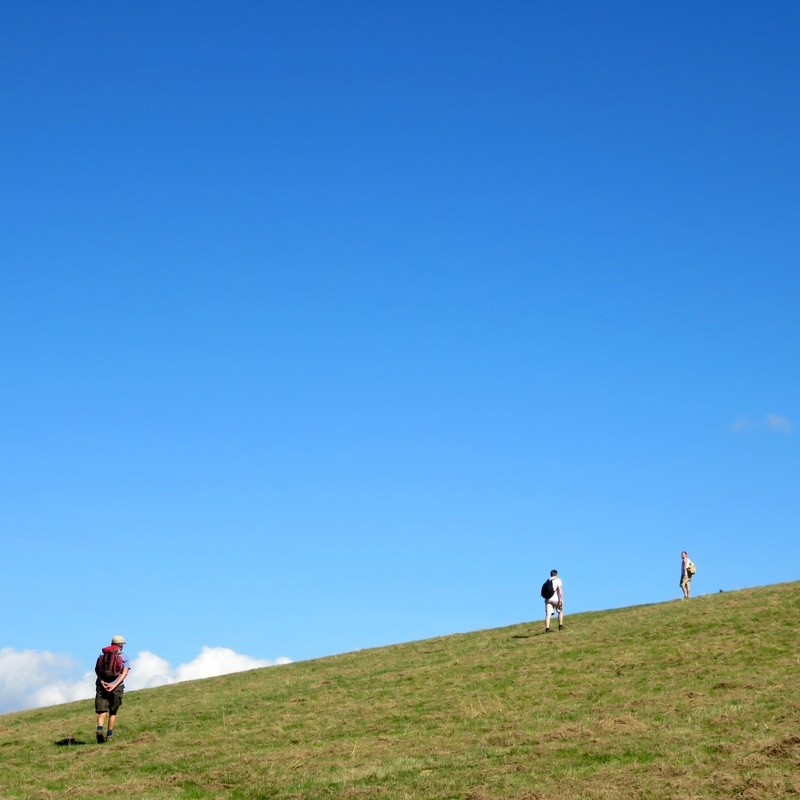 people, hill and bright blue sky