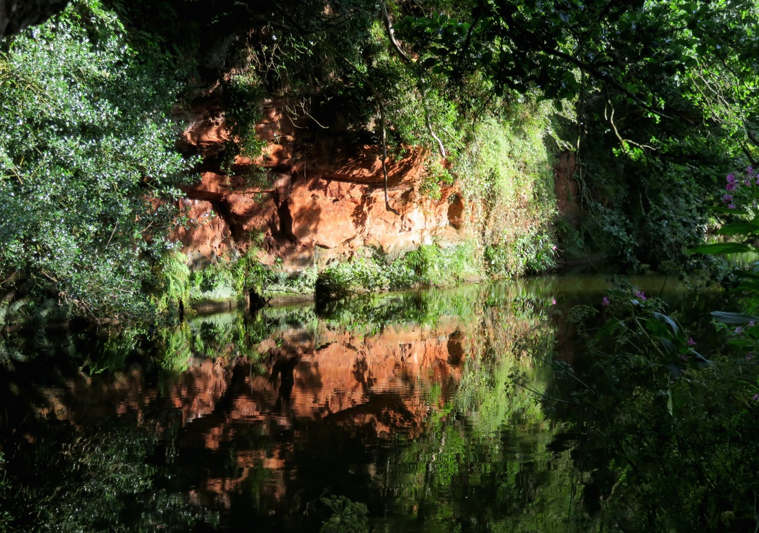 red cliff reflected in river