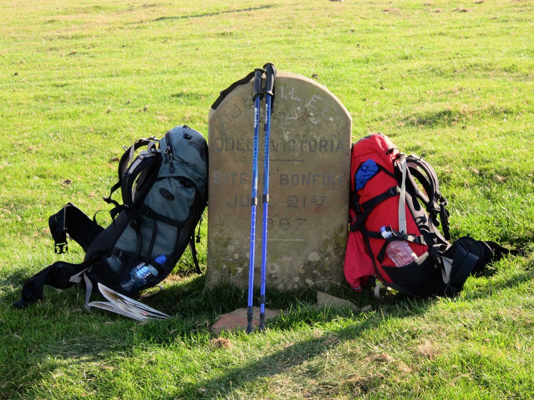 Backpacks, walking poles, map and Jubilee Stone