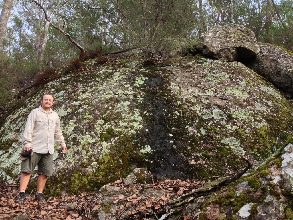 person beside big boulder