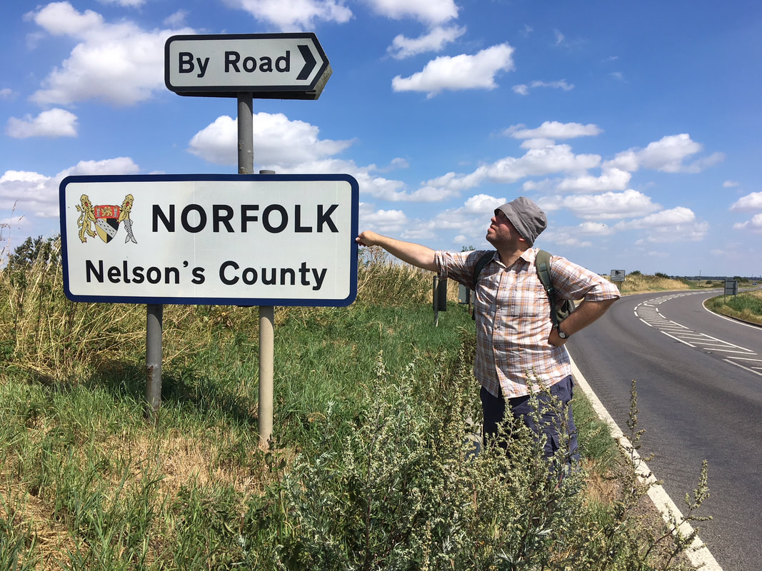 Person standing beside a sign saying NORFOLK Nelson's Country - and By Road