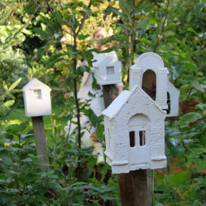 small ceramic chapels on posts