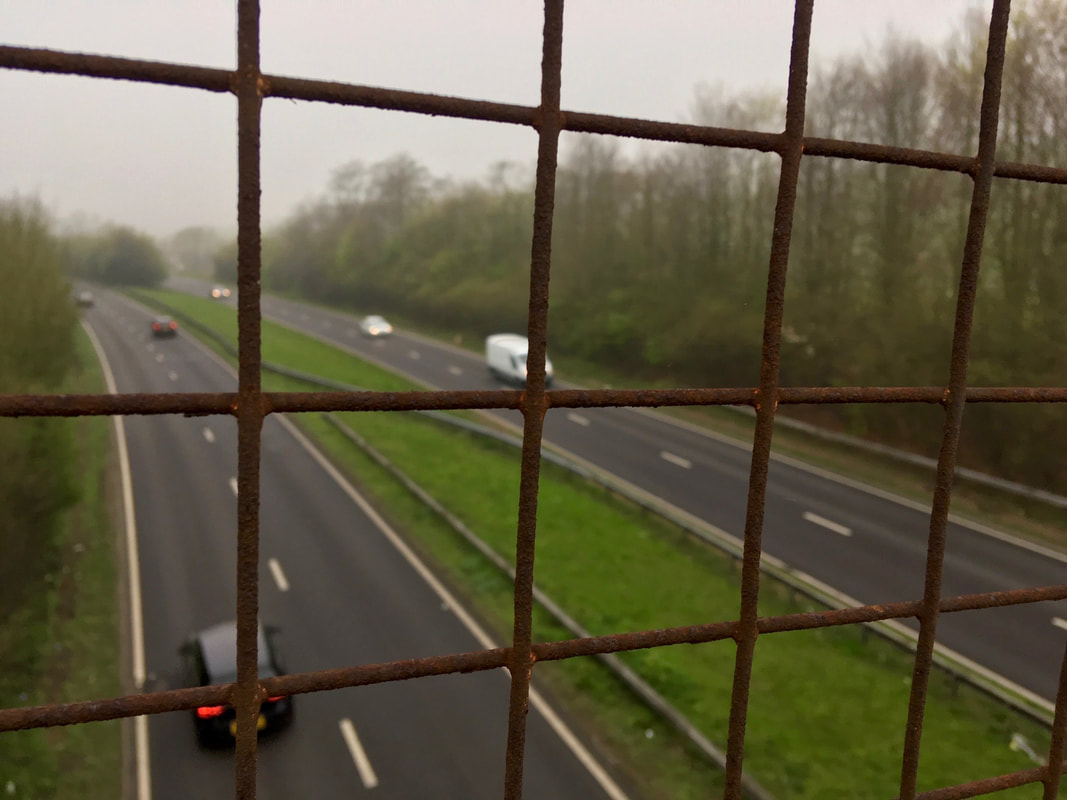 Dual carriageway seen through wire mesh from above