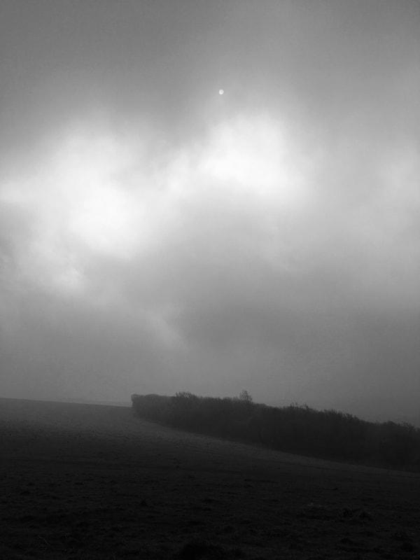 Black and white landscape with sun in clouds