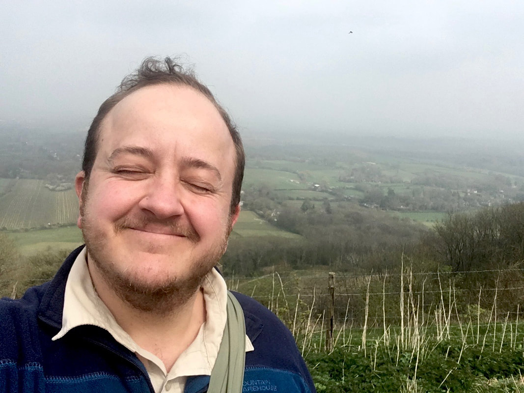 Selfie of person smiling with eyes closed and landscape behind
