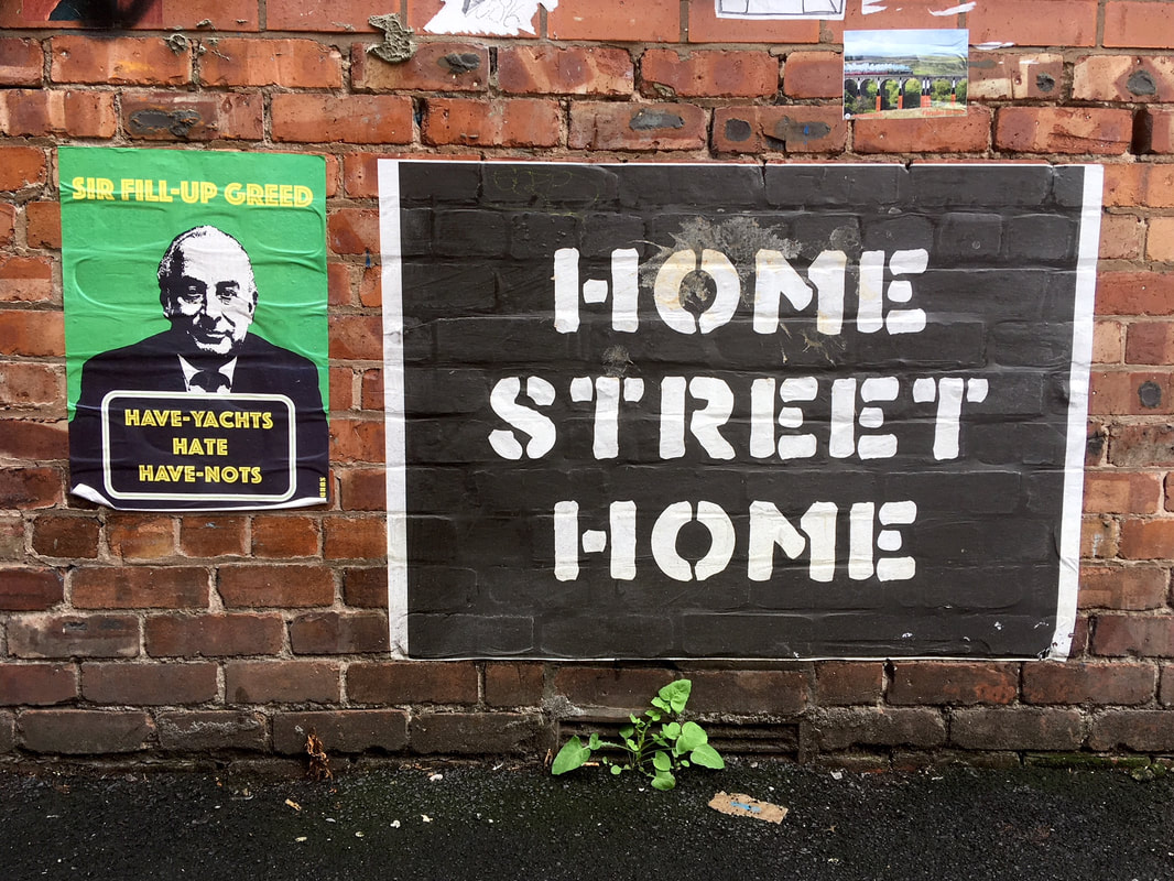 Posters on brick wall - one says HOME STREET HOME