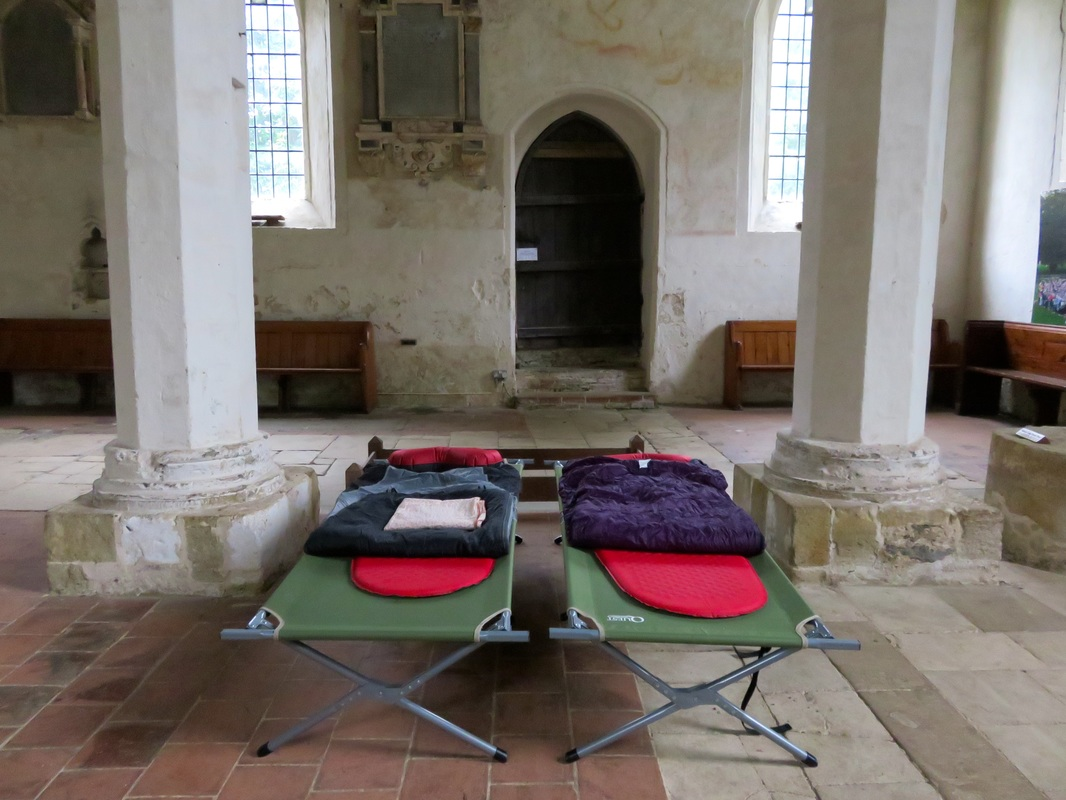 Two camp beds with sleeping gear in a large church