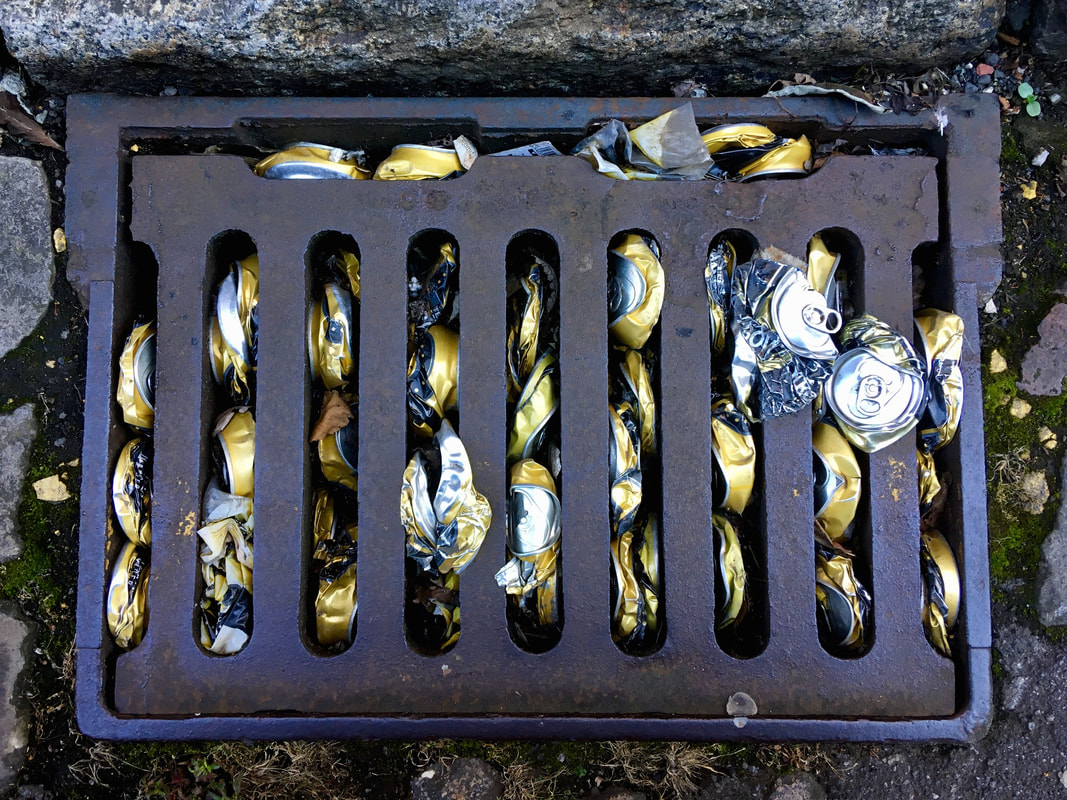 Gold cider cans stuffed into a metal grate