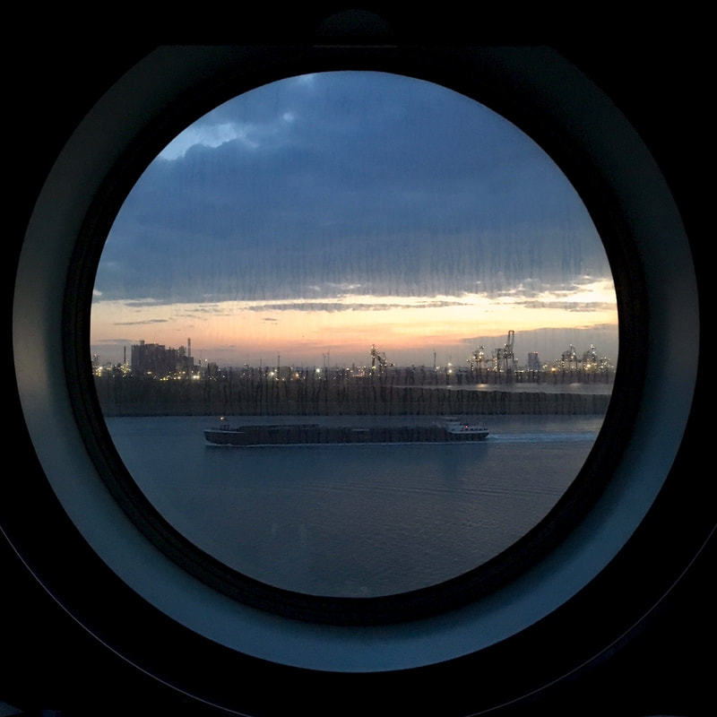 water and lights and sunset through a round window