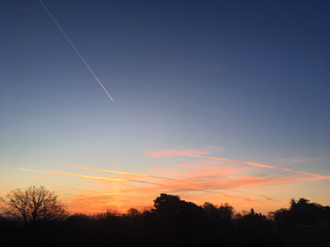 orange sunrise sky with contrails
