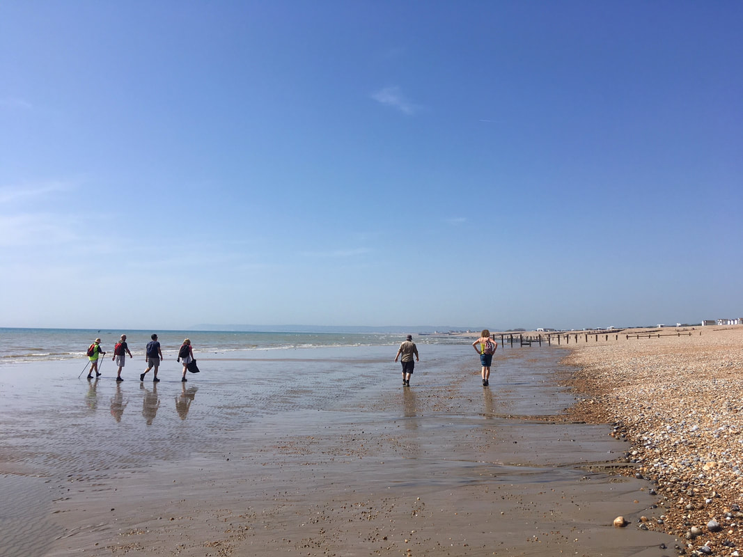 people walking along beach at low tide